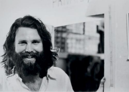 Jim Morrison as a bearded twenty-something, smiling.